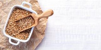 Mestolo di legno pieno dei semi del grano su fondo di legno bianco Immagini Stock Libere da Diritti