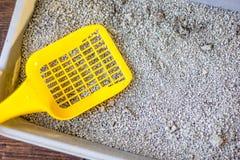 Mestolo di plastica giallo sul cestino per i rifiuti grigio, riempito dalla sabbia blu della lettiera Fotografia Stock Libera da Diritti