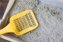 Mestolo di plastica giallo sul cestino per i rifiuti grigio, riempito dalla sabbia blu della lettiera Immagine Stock Libera da Diritti