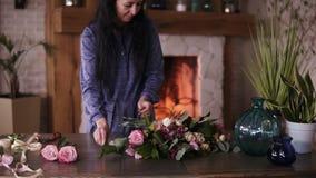 Mestre adulto do florista que arranja as flores e as plantas grandes da variedade no contador para a composição futura oficina filme
