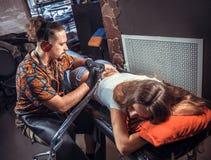 Mestre da arte de tattooing que cria uma tatuagem em seu cliente Imagens de Stock