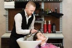 Mestre do cabelo do homem que molha o cabelo de uma menina com um chuveiro em um estúdio do cabelo foto de stock