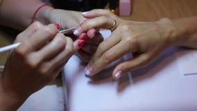 Mestre do tratamento de mãos que cria um inclinação com uma escova no prego do anel-dedo do cliente vídeos de arquivo
