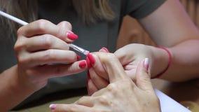 Mestre do tratamento de mãos que cria um inclinação com uma escova no prego do dedo indicador do cliente vídeos de arquivo