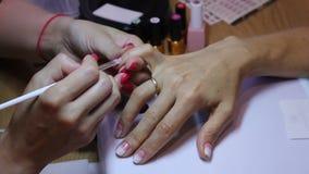 Mestre do tratamento de mãos que cria um inclinação com uma escova no prego do dedo pequeno do cliente Arte de pintura do prego vídeos de arquivo