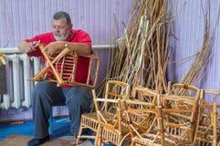 Mestre do vime-trabalho que faz um tamborete Foto de Stock Royalty Free