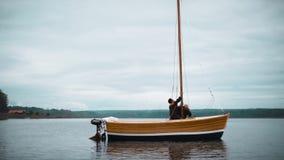 Mestre e seu trabalho assistente no veleiro de madeira no lago que instala o mastro video estoque
