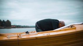 Mestre e seu trabalho assistente no veleiro de madeira no rio video estoque