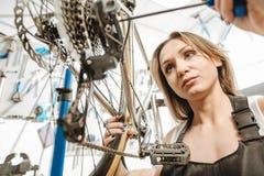 Mestre encantador trabalhador que fixa a bicicleta na oficina de reparações Fotografia de Stock