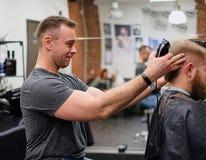 Mestre no corte do cabelo Bom corte de cabelo do bom humor para um cliente satisfeito fotografia de stock