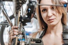 Mestre novo observador que renova a bicicleta na oficina Imagens de Stock