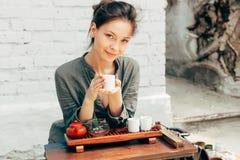 Mestre oriental da cerimônia de chá com a parede de tijolo branca no fundo Tea party tradicional na natureza com a mulher vestida imagem de stock