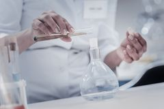 Mesuré vers le haut du regard sur le liquide de versement de chimiste féminin dans le flacon image stock
