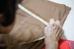 Mesure de main de grand-maman le dessin sur le tissu Photographie stock