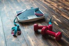 Mesure le ruban métrique et les haltères d'isolement sur le plancher en bois à la maison photo stock