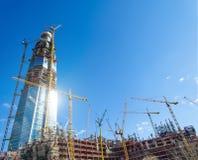 Mesurez le bâtiment actif de gratte-ciel, éclat du soleil sur les fenêtres, grues contre le ciel bleu photographie stock libre de droits