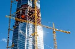 Mesurez le bâtiment actif de gratte-ciel, éclat du soleil sur les fenêtres, grues contre le ciel bleu image libre de droits