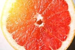 Metà affettata pompelmo su fondo grigio Macro degli agrumi Copi lo spazio, vista superiore Concetto dell'alimento di estate immagini stock