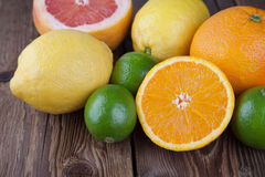 A metà arancio con altri frutti su legno Fotografia Stock