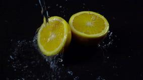 A metà arancio con spruzza dell'acqua su un fondo nero Movimento lento stock footage