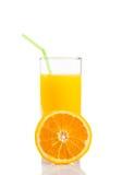 A metà arancio davanti a vetro di succo d'arancia con paglia su fondo bianco immagine stock