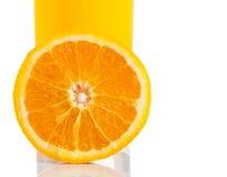 A metà arancio davanti a vetro di succo d'arancia su fondo bianco fotografia stock libera da diritti
