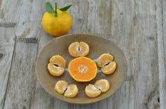Metà arancio fresca del taglio e sbucciata in piatto su fondo di legno fotografia stock