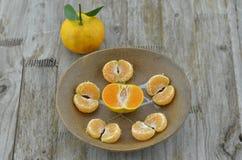 Metà arancio fresca del taglio e sbucciata in piatto su fondo di legno fotografia stock libera da diritti