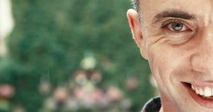 Metà del fronte dell'uomo attraente con i bei occhi e del sorriso in pioggia metraggio 4k Sta guardando in camera video d archivio
