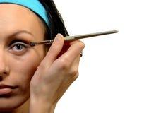 Metà del fronte della donna che applica l'ombra di occhio Fotografia Stock