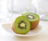 Metà del kiwi su un piatto Fotografie Stock Libere da Diritti
