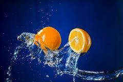 Metà del limone e della spruzzata di acqua su fondo blu Immagini Stock Libere da Diritti