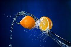 Metà del limone e della spruzzata di acqua su fondo blu Fotografia Stock Libera da Diritti