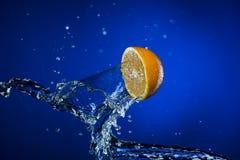 Metà del limone e della spruzzata di acqua su fondo blu Fotografie Stock Libere da Diritti