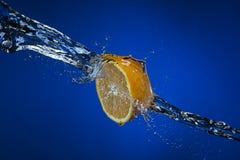 Metà del limone e della spruzzata di acqua su fondo blu Immagini Stock