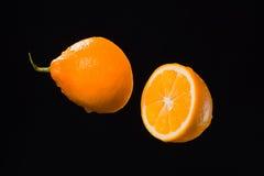 Metà del limone e gocce di acqua su fondo nero Fotografie Stock