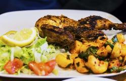 Metà del pollo arrostito al carbone di legno con insalata e le patate piccanti immagine stock libera da diritti