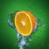 Metà dell'arancia e della spruzzata di acqua su fondo verde Fotografie Stock