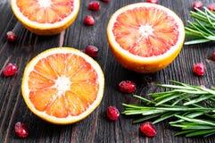 Met? dell'arancia sanguinella, dei semi del melograno e dei rosmarini su un fondo di legno scuro Ingredienti per le bevande di es immagini stock libere da diritti