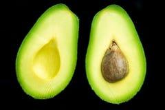 Metà dell'avocado su fondo scuro, disposizione piana immagine stock libera da diritti