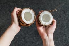 Metà della tenuta di una noce di cocco Immagini Stock