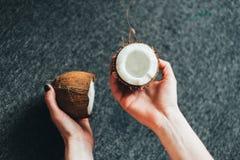 Metà della tenuta di una noce di cocco Immagini Stock Libere da Diritti