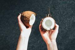Metà della tenuta di una noce di cocco Fotografie Stock