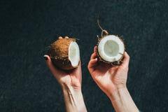 Metà della tenuta di una noce di cocco Immagine Stock