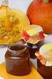 Metà della zucca tagliata e di tre vasi della marmellata d'arance Fotografia Stock