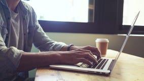 Metà di colpo dell'uomo casuale che scrive sul computer portatile archivi video