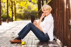 Metà di compressa della donna di età Fotografia Stock