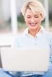 Metà di computer portatile della donna di età Fotografia Stock Libera da Diritti