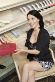 Metà di donna adulta allegra con la scatola delle calzature in negozio di scarpe Fotografie Stock Libere da Diritti