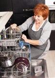 Metà di donna che piega i piatti nella lavastoviglie Fotografie Stock Libere da Diritti